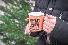 妇女拿着橙色咖啡杯 热的冬天饮料在手上 免版税图库摄影