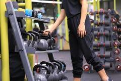 妇女拿着烧伤油脂的训练手kettlebell在体育健身房、健康生活方式和体育概念的身体 免版税库存图片