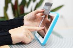 妇女拿着片剂个人计算机的和信用卡,互联网购物浓缩 免版税库存图片