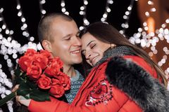妇女拿着玫瑰并且微笑着,当拥抱人时 免版税库存图片