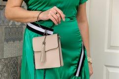 妇女拿着精美灰棕色一台小时髦的袋子传动器  免版税库存图片
