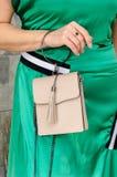 妇女拿着精美灰棕色一台小时髦的袋子传动器  免版税图库摄影
