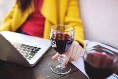 妇女拿着红葡萄酒片剂和膝上型计算机在街道咖啡馆 免版税库存图片