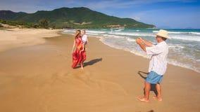 妇女拿着胳膊步行的女儿在海滩祖父照片 股票视频