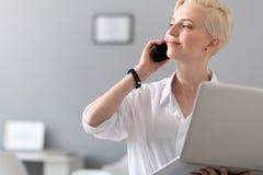 妇女拿着膝上型计算机和谈话在电话 库存图片