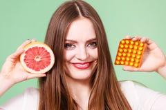 妇女拿着葡萄柚和药片天线罩包装维生素C 库存图片