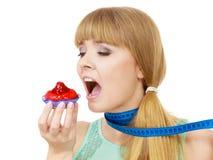 妇女拿着设法的杯形蛋糕抵抗诱惑 库存照片