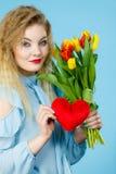 妇女拿着郁金香和红色心脏 库存图片