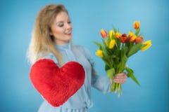 妇女拿着郁金香和红色心脏 免版税库存图片
