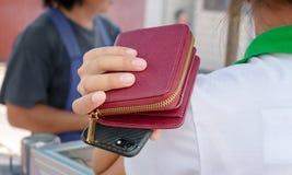 妇女拿着钱包和智能手机在肩膀未察觉对钱包抢夺者的危险 免版税库存照片