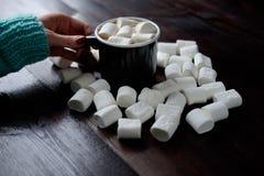 妇女拿着黑咖啡的` s手用蛋白软糖在中 库存照片