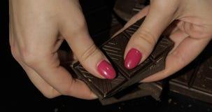 妇女拿着黑巧克力块 r 免版税库存照片