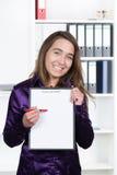 妇女指向有笔的一张剪贴板 免版税库存图片