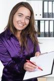 妇女指向有笔的一张剪贴板 免版税库存照片