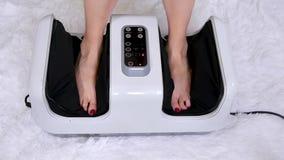 妇女按摩她有一个电子按摩器的疲乏的腿,坐在椅子后 现代医疗技术,健康 股票视频
