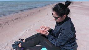 妇女排序琥珀色的片断坐海滩在海附近在大风天 股票录像