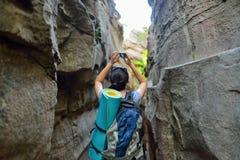 妇女探索狭窄的峡谷在夏日和做照片的远足者背包徒步旅行者在智能手机,从后面的看法 免版税库存照片