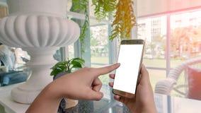 妇女接触一个智能手机 免版税库存图片