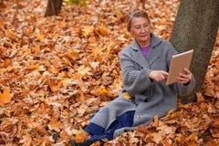 妇女接触有她的手指的片剂 坐在一棵树下在秋天的一个公园 免版税库存照片