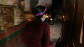 妇女接触转动的大西藏佛教地藏车 影视素材