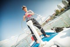 妇女控制游艇 库存图片