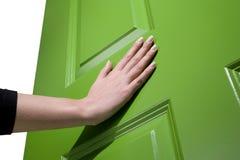 妇女推挤开放一个绿色的门 库存照片