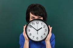 妇女掩藏她的在时钟后的面孔,摆在粉笔板、时间和教育概念,绿色背景,演播室射击 库存照片