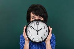 妇女掩藏她的在时钟后的面孔,摆在粉笔板、时间和教育概念,绿色背景,演播室射击 免版税图库摄影