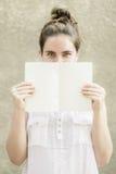 妇女掩藏的一半她的在空的白皮书笔记本后的面孔 免版税库存照片