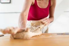 妇女揉的面团在厨房里 图库摄影