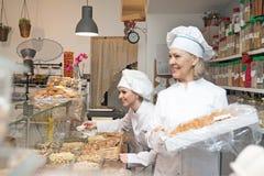 妇女提供新鲜和酥皮点心在面包店 免版税库存照片