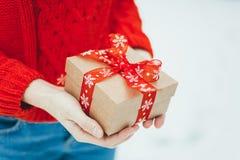 妇女提出一项圣诞节礼物 图库摄影