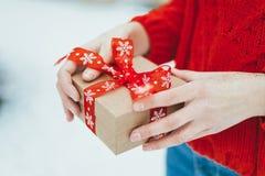 妇女提出一项圣诞节礼物 库存照片