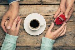 妇女握人的手并且采取他的订婚的礼物 免版税图库摄影