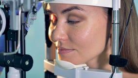 妇女握眼睛开放在光学检查期间在眼科医生办公室 股票录像