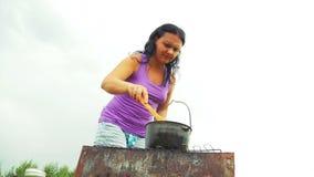 妇女搅动与一把木匙子的汤在火的一个水壶 他移动远离抽烟 影视素材