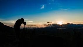 妇女摄影师和美好的日出 免版税库存照片