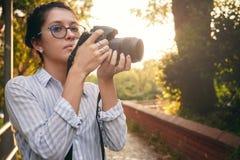妇女摄影师,为风景照相在日落 免版税图库摄影