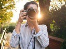 妇女摄影师,为风景照相在日落 免版税库存图片