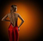 妇女摆在性感的红色礼服的赤裸后面,女子般地的时装模特儿 图库摄影