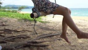 妇女摇摆在木摇摆放松并且享用在热带海滩有蓝色海和天空背景在一个夏日在泰国的普吉岛 股票录像