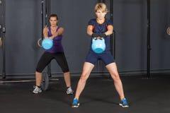 妇女摇摆的kettlebell -健身训练 库存照片