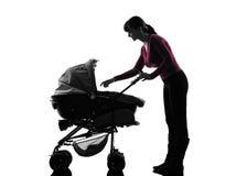 妇女摇篮车婴孩剪影 免版税图库摄影