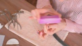 妇女擦亮她的与抛光的钉子,并且指甲锉前面取消紫胶 特写镜头手 股票视频