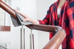 妇女擦亮木台阶扶手栏杆 库存图片