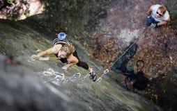 妇女攀岩与马枪和绳索 免版税库存图片