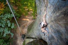 妇女攀岩运动员在岩石墙壁上上升 图库摄影