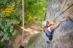 妇女攀岩运动员在岩石墙壁上上升 免版税库存图片