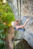 妇女攀岩运动员在岩石墙壁上上升 库存图片