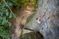 妇女攀岩运动员在岩石墙壁上上升 库存照片